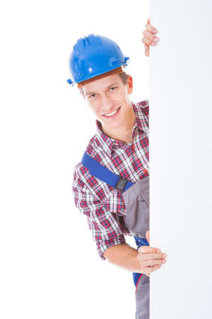 Portrait Of Young Male Worker Holding Placard Over White  photo