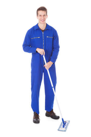 Young Male Worker In Boilersuit Cleaning Floor With Mop photo