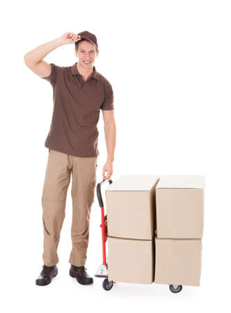 Happy Delivery Man Standing With Boxes On Hand truck Over White  photo