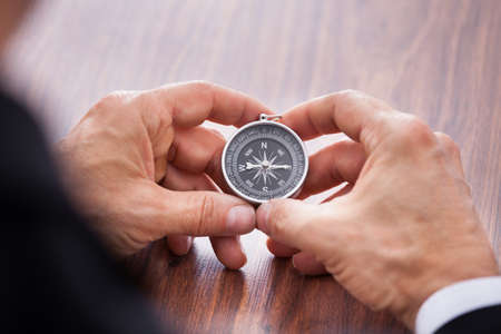 Close-up Of Hand Holding Compass On White  photo