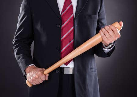 Close-up Of Businessman Holding Baseball Bat Over Black Background