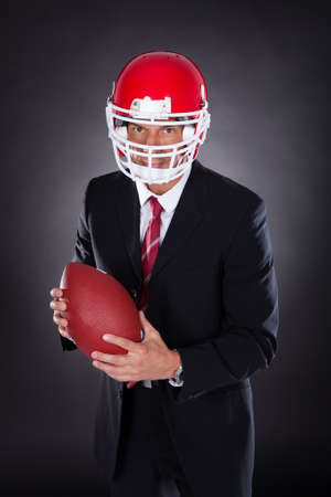 rugby player: Mature Businessman Wearing Helmet Holding Rugby Ball