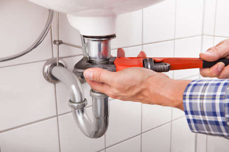 maintenance: Close-up Of Male Plumber Fitting Sink Pipe In Bathroom Stock Photo