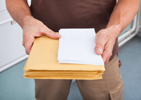 postman: Close-up Photo Of Mature Postman Holding Letters Stock Photo