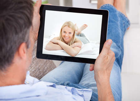 Close-up Of A Man Video Chatting With Young Woman photo