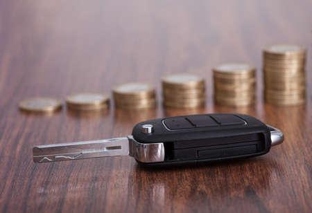 나무 테이블에 누적 된 동전의 앞의 자동차 키의 근접