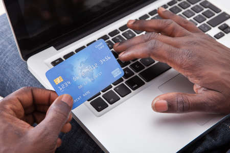 Close-up Of Hand Holding Credit Card And Shopping Online Stock Photo