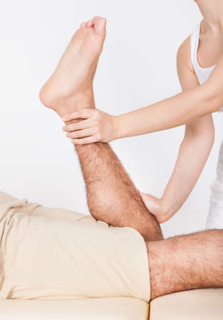Young Man Lying On Table Getting Foot Massage From Masseuse Stock Photo - 25156375