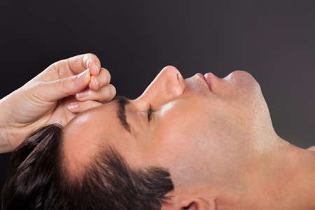 Close-up Of A Young Man Getting Acupuncture Treatment photo