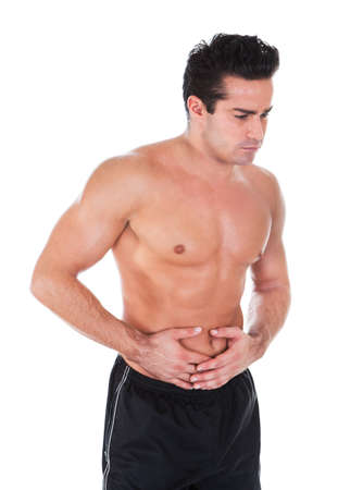 constipation symptom: Portrait Of Young Shirtless Man Having Stomach ache