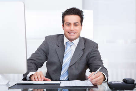 Portrait Of Young Businessman Using Computer At Office Stock Photo - 25149584