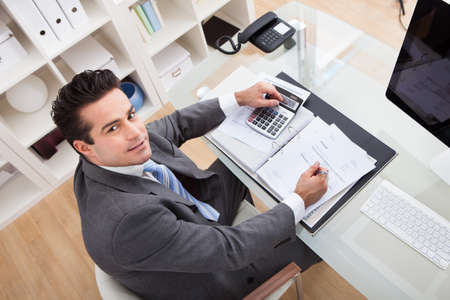 Businessman Calculating Documents Using Calculator In Office