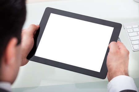 Close-up Of A Businessman Holding Digital Tablet On Desk photo