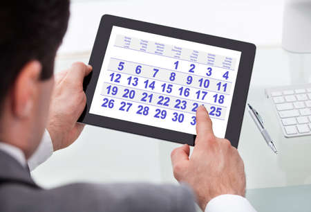 Primer plano de un empresario mirando el calendario En Tableta digital