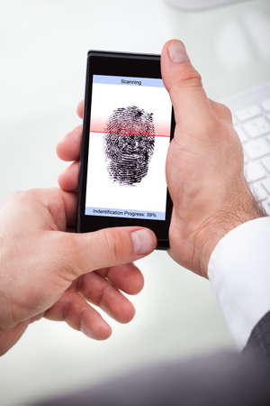 fingermark: Close-up Of A Businessman Holding Cellphone Scanning Finger