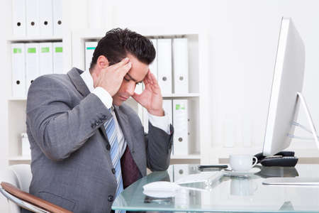 Young Businessman In Office At Desk Suffering From Headache photo