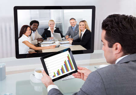 Young Businessman Analyzing Graph While Chatting With His Colleagues photo