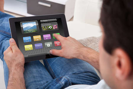 Close-up Of Man Holding Digital Tablet With Colorful Icons photo