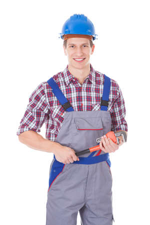Happy Worker Holding Toolkit And Wrench Over White Background photo