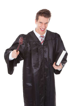 Portrait Of Frustrated Judge Holding Gavel And Book Over White  Stock Photo