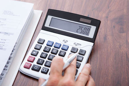 Close-up Of A Businessman Calculating Finance At Desk photo