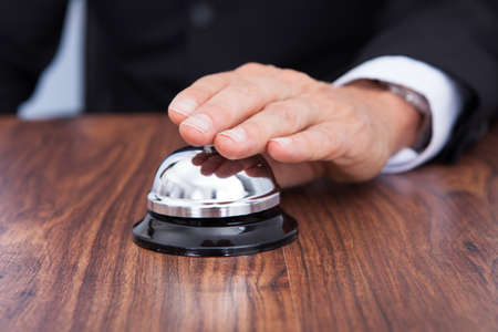 Close-up Of Hand Ringing Bell Kept On Wooden Table