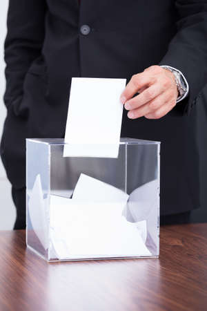 Happy Mature Businessman Inserting Ballot In Transparent Box photo