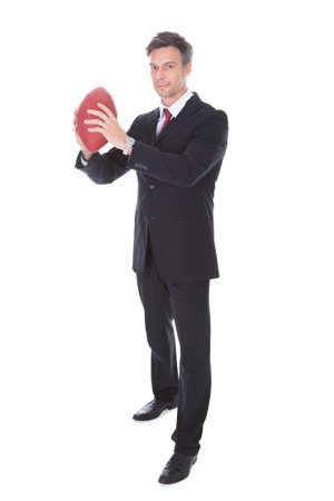 Portrait Of Mature Businessman Holding Rugby Ball Over White  photo