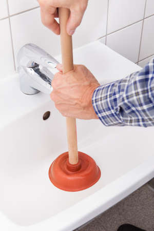 Portrait Of Male Plumber Using Plunger In Bathroom Sink photo