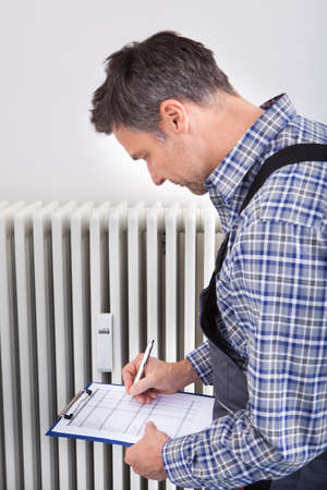 boiler suit: Portrait Of Male Plumber Taking Reading On Clipboard Of Machine Stock Photo