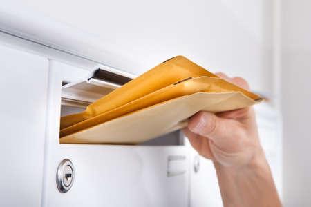 cartero: Primer Plano De Postman Poner letras en Buz�n Foto de archivo