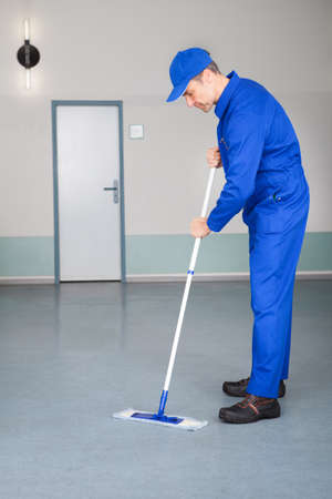 Happy Mature Male Worker Cleaning Floor With Mop photo