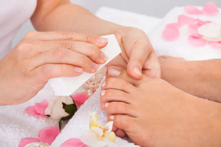 Close-up Of Beautician Hand Filing The Nails Of Woman In Salon Stock Photo - 25150100
