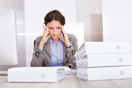 Portrait Of Stressed Businesswoman Looking At Stack Of Folders photo