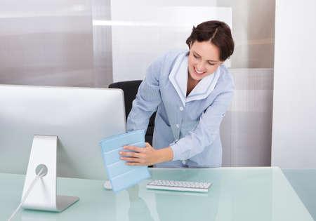 profesionálové: Portrét šťastná žena Janitor čištění stolu v kanceláři