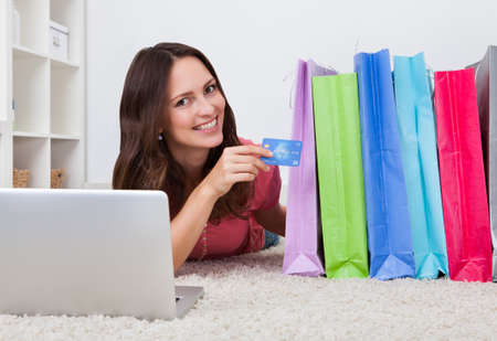 Smiling Young Woman Lying On Carpet Besides Row Of Shopping Bags photo