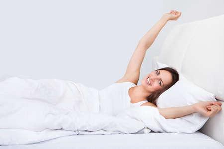 gente durmiendo: Retrato de mujer joven con la mano levantada que miente en cama Foto de archivo