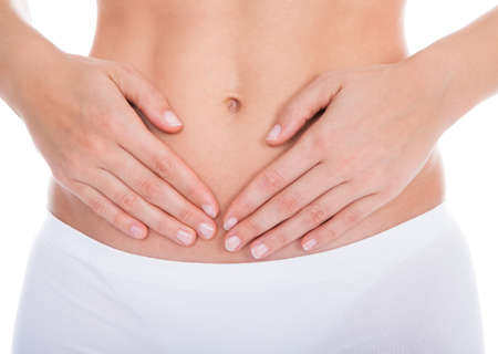 hurting: Young Woman With Pain In Her Stomach Isolated Over White Background Stock Photo