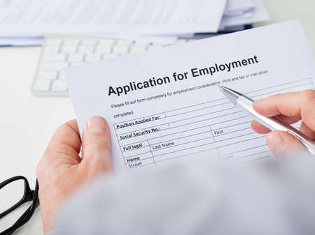 Close-up Of Hand Filling Application For Employment photo