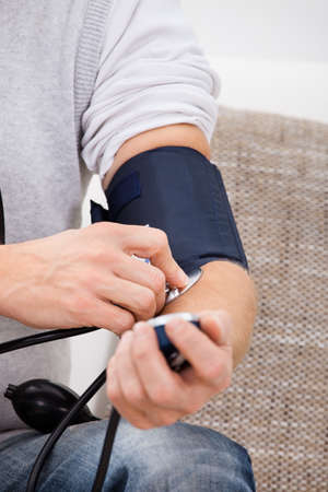 own blood: Man Sitting On Couch Checking His Own Blood Pressure