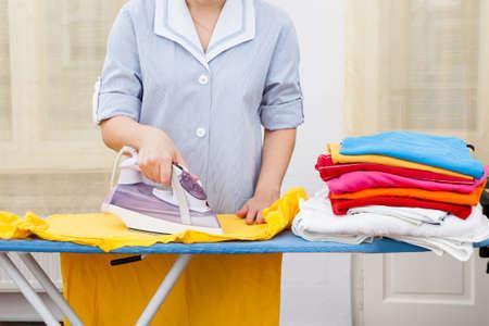 sirvienta: Close-up de dama de planchado de ropa a bordo de planchado
