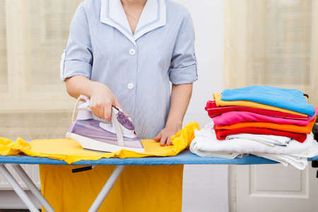 iron curtains: Close-up Of Maid Ironing Clothes On Ironing Board Stock Photo