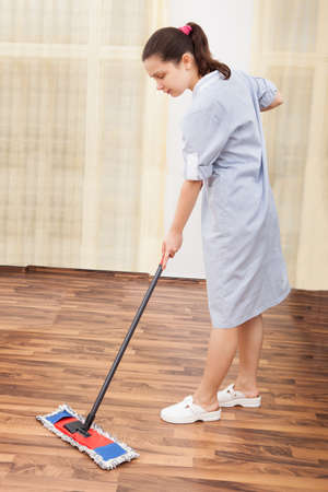 Portrait Of Young Maid In Uniform Cleaning Wooden Floor photo