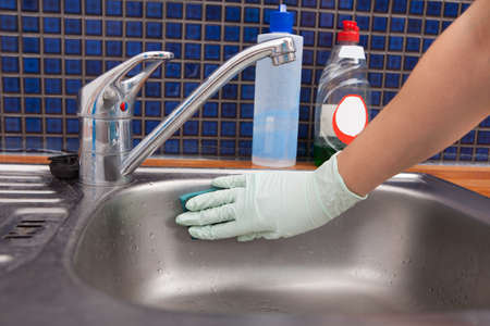 handglove: Close-up Of A Woman Wearing Apron Cleaning Kitchen Sink