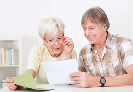 old people smiling: Portrait Of Happy Senior Couple Reading Letter Together
