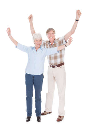 Happy Senior Couple Raising Hand Over White  photo