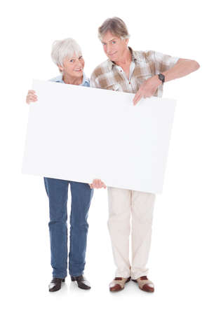 woman holding card: Senior Lovely Couple Holding Together A Blank White Board Over White  Stock Photo