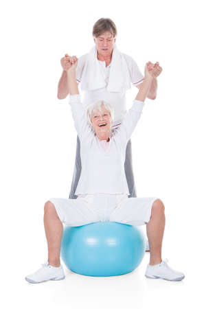 Happy Senior Couple Exercising With Pilates Ball On White Background photo