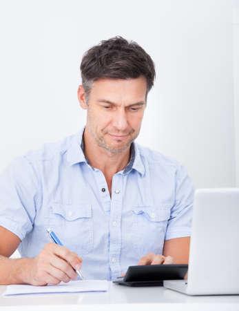 Portrait Of A Happy Mature Man Calculating Finance photo
