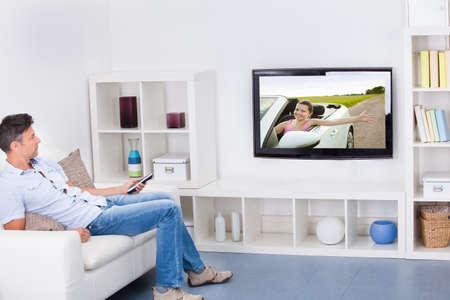 �lterer Mann sitzt auf Couch Fernsehen